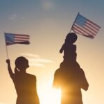silhouette of family wave US flag, immigration