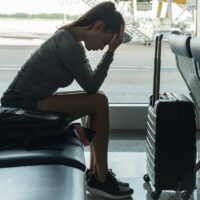 A passenger waiting at the airport terminal stressed out at tired.